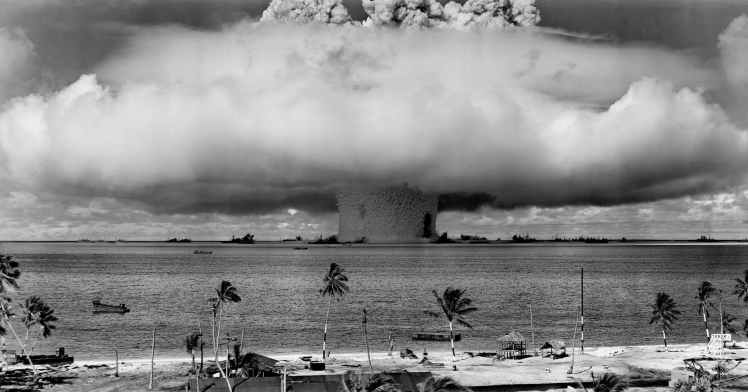 grayscale photo of explosion on the beach